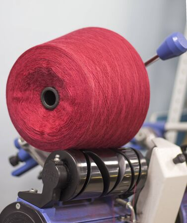 machine for winding yarn with red thread in the production.