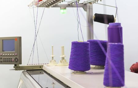 purple threads on the knitting machine knitting process.