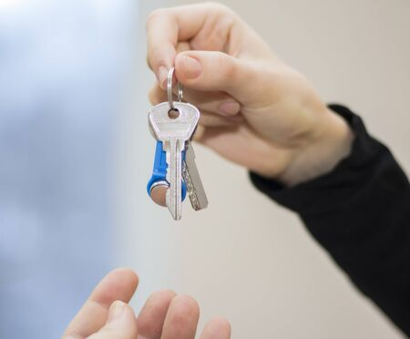 The realtor passes the keys to the apartment to the clients.the concept of selling or renting a home. Imagens
