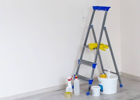 a stepladder with paint cans and tools in a bright renovated room with a copy of the space.