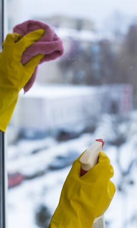 The concept of a cleaning woman in yellow gloves washes a window, close-up.