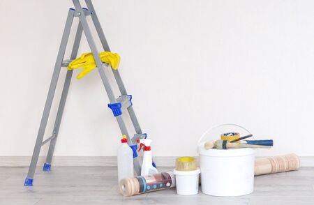 a stepladder with paint cans and tools against a light renovated wall with a copy of the space.