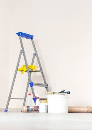 a stepladder with paint cans and tools in a bright renovated room.