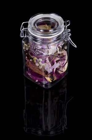 dry decorative flower petals in a jar on a black background with reflection. Imagens