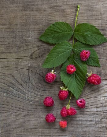 Ripe raspberries on the old wooden surface of the table. Mortgage the apartment..