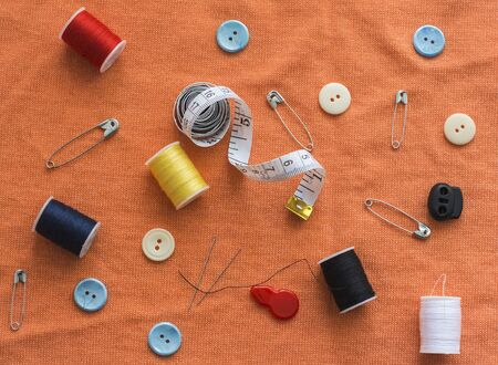 sewing accessories on an orange knitted background flat lay. Imagens