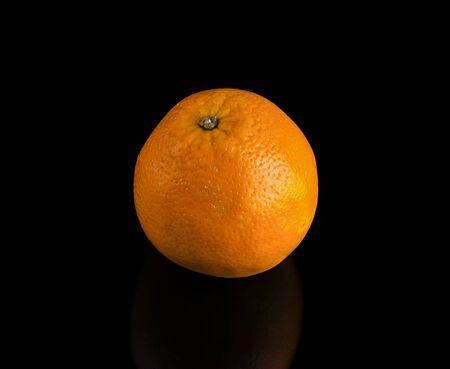 one bright juicy orange on a black background.