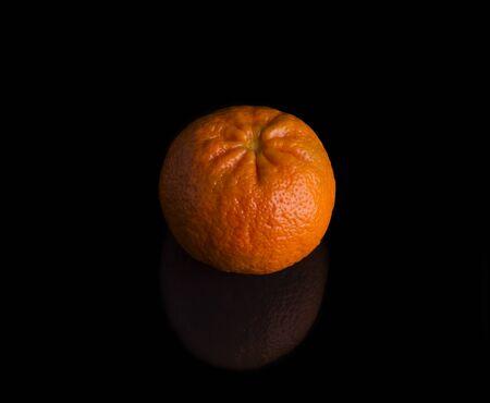 one bright juicy tangerine on a black background. Reklamní fotografie