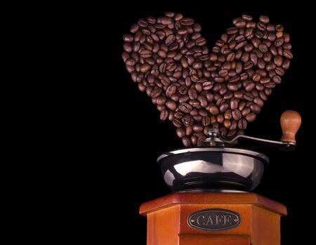 coffee beans in the shape of a heart are poured into a coffee grinder on a black background with a copy of the space.