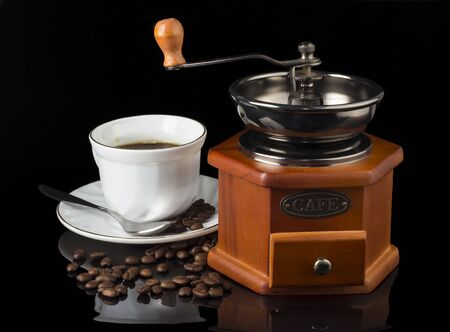coffee grinder with a Cup of coffee and coffee beans scattered between them on a black background.