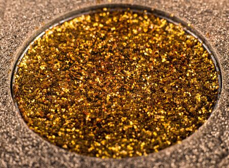 festive eye shadow in gold color in a shiny package, macro