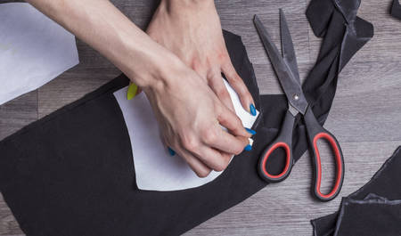 a woman draws paper details with chalk on a black fabric for sewing protective masks at home.