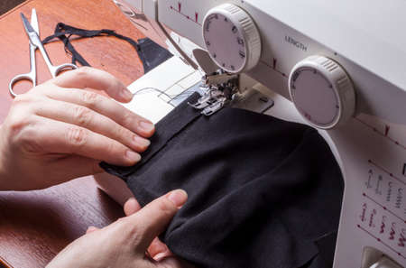 a woman joins the details of a protective mask at home on a sewing machine.