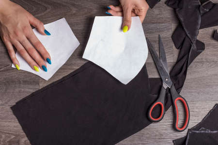 a woman holds paper parts over a black cloth, for sewing protective masks at home.