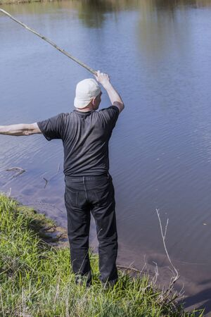 A fisherman stands and catches fish on the Bank of the river.