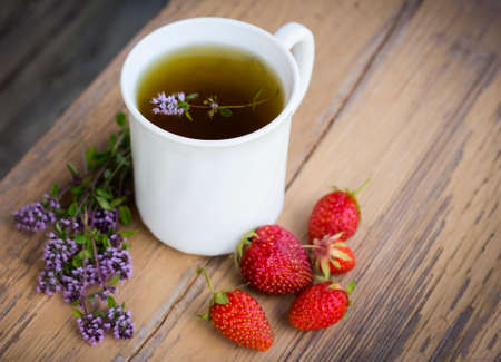 White tea Cup with grass thyme and strawberries on a wooden background top view. 스톡 콘텐츠