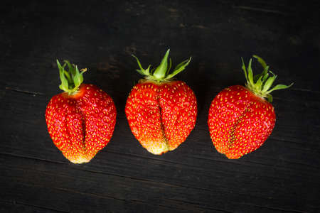 three red ripe strawberries on a black wooden background top view.