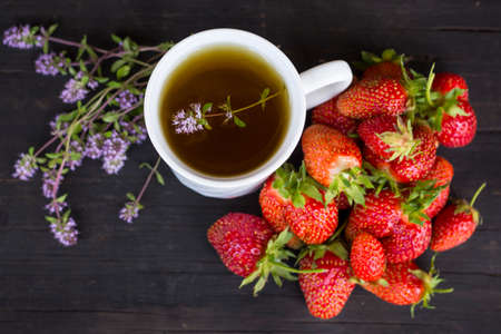 green tea with thyme and lots of red strawberries on a wooden background.