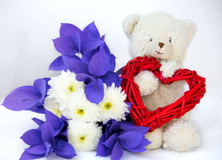 a Valentines day card or other holiday with a bear and a heart and a bouquet of flowers