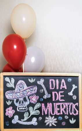 the frame is painted with a skull and flowers Day of the dead, balloons in the background