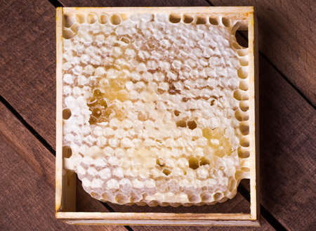 honeycomb in a frame with honey on a wooden table Imagens
