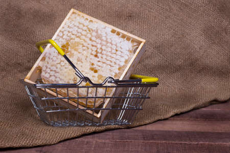 honeycomb in an iron basket on a wooden table on a background of burlap