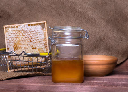 a jar of honey combs in an iron basket and a clay plate on a wooden table against a background of burlap Imagens