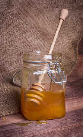 glass jar with honey and wooden spoon on the background of burlap