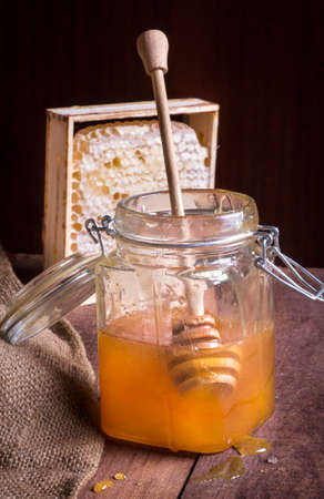 glass jar of honey with a wooden spoon and honeycomb in the background, on a dark background