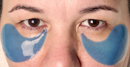 woman's face close up during Spa treatment with blue patches under her eyes. Imagens