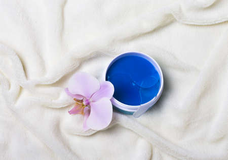 cosmetic jar with blue eye patches with an Orchid on a white fur background