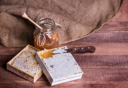 honey in a glass jar and honeycomb with a knife on a wooden background and burlap with a copy of the space