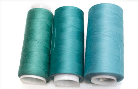 sewing threads in turquoise shades on a white background