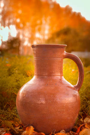 old clay jug on the background of autumn nature
