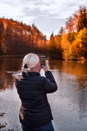 a woman takes photos of the autumn landscape on her smartphone