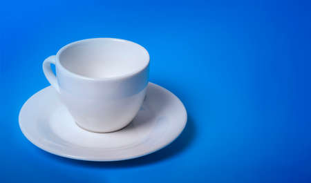 illuminated empty white Cup on a blue background with a copy of the space