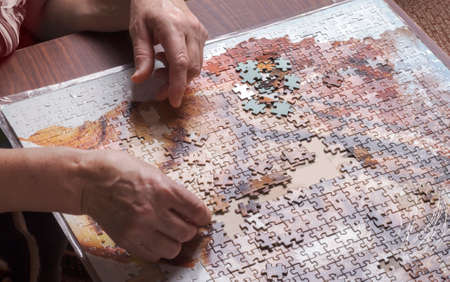 hands of an elderly woman collecting puzzles on the table