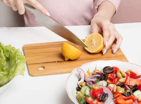 A woman halves a lemon on a cutting Board to add lemon juice to a Greek salad.