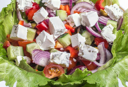 ingredients in fresh Greek salad in a salad bowl on a white background
