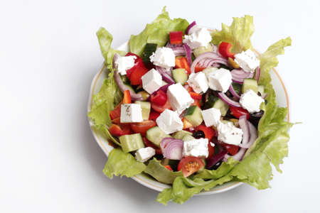 fresh Greek salad in a salad bowl on a white background