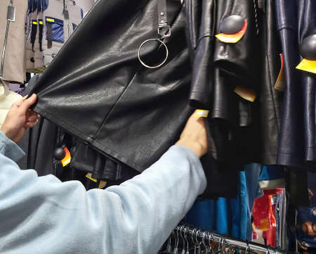 a girl chooses a leather skirt in a store Imagens