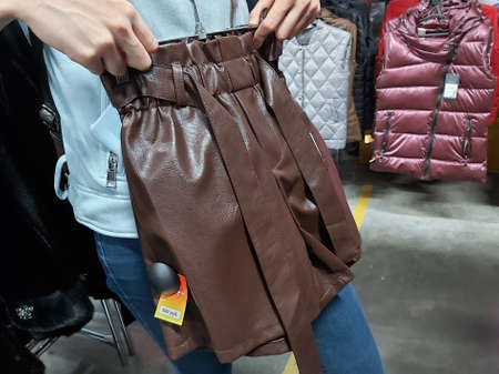 a girl chooses a leather skirt in the store, trying on herself Imagens
