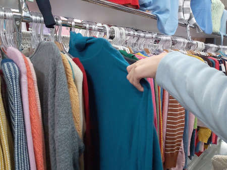 girl chooses warm knitted jumpers in the store Imagens