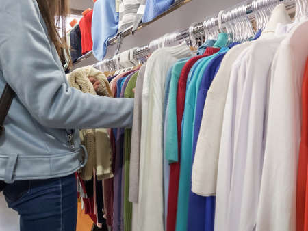 girl chooses clothes in the store, hanging on hangers