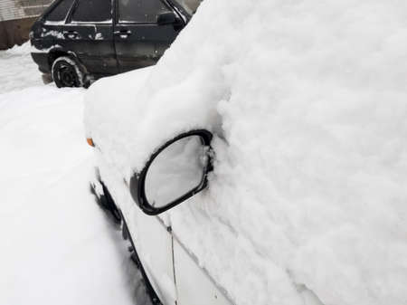 the car is covered with snow and only the mirror can be seen from under the snow Imagens