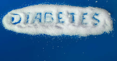 the word diabetes is written on sugar sand on a blue background with a copy of the space Imagens