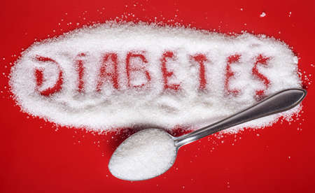 the word diabetes is written on sugar sand with a spoon on a red background with a copy of the space