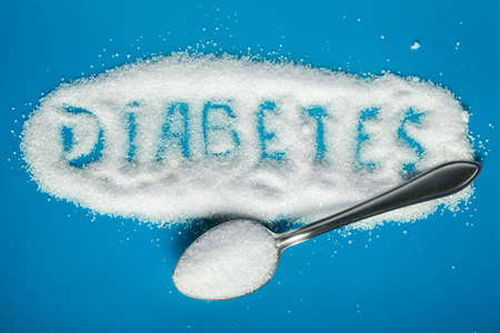 the word diabetes is written on sugar sand with a spoon on a blue background with a copy of the space Imagens