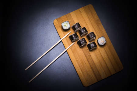 wooden board with rolls and chopsticks on black background