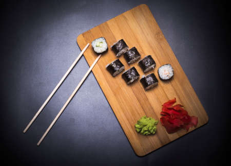 wooden board with Japanese fish rolls, ginger and wasabi and chopsticks on black background